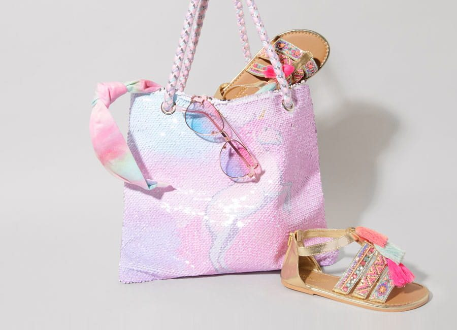 Complete their fun-in-the-sun look with everything from unicorn beach bags to metallic sandals.