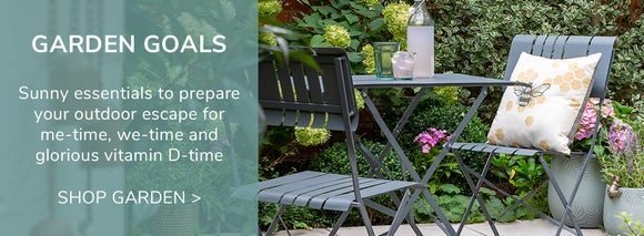 Garden Goals. A 2 seat grey bistro set in a small garden space with drinks on the table and a bee cushion on one of the chairs. Shop Garden >