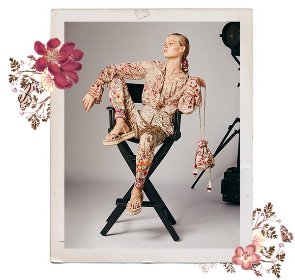 Model wearing CAMILLA leopard and pink floral ruffle blouse and matching pants sitting in directors chair