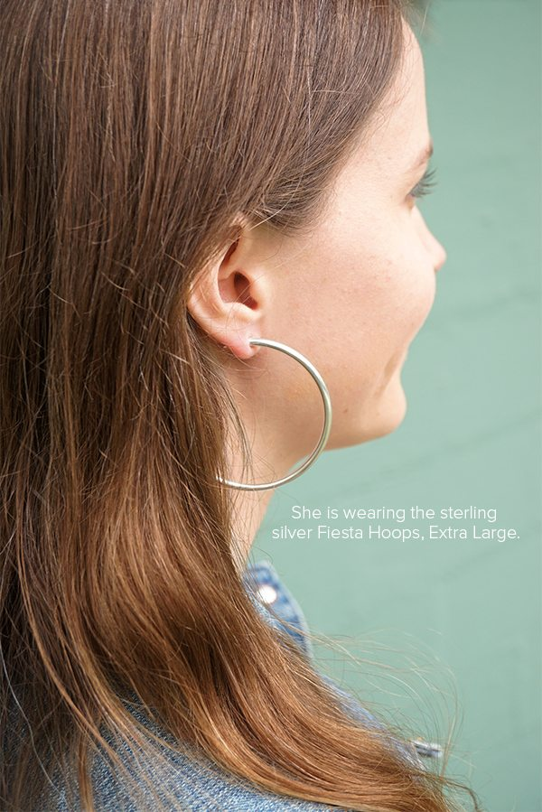 She is wearing the sterling silver Fiesta Hoops, Extra Large.