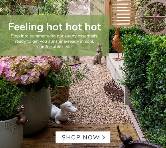 Hot Weather Essentials. Garden path with multiple garden decor items including a sausage dog planter, bird bath and hare ornament. Shop Now >